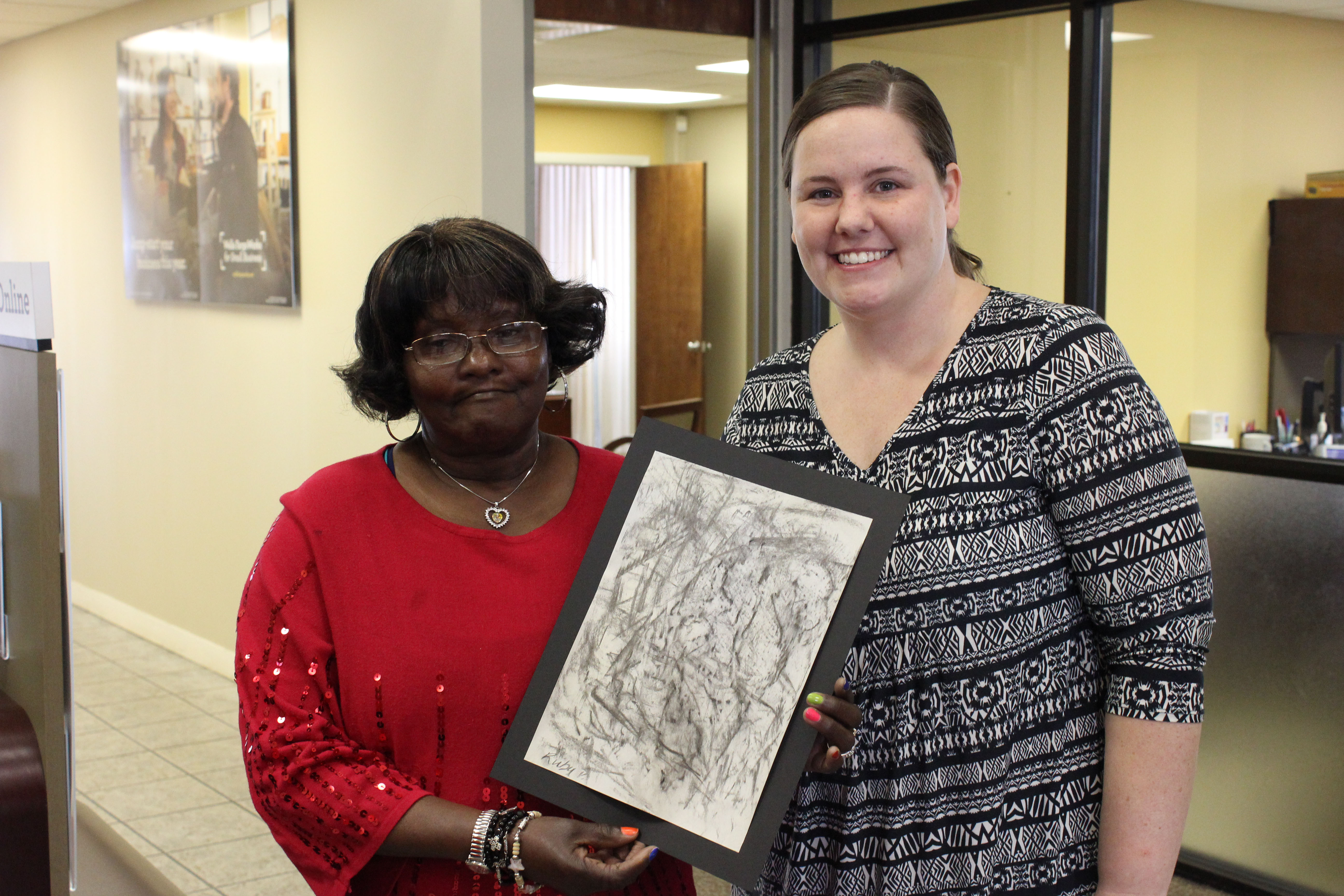 Sunland resident Ruby P., left, proudly displays her willow charcoal rubbing with a Wells Fargo employee.