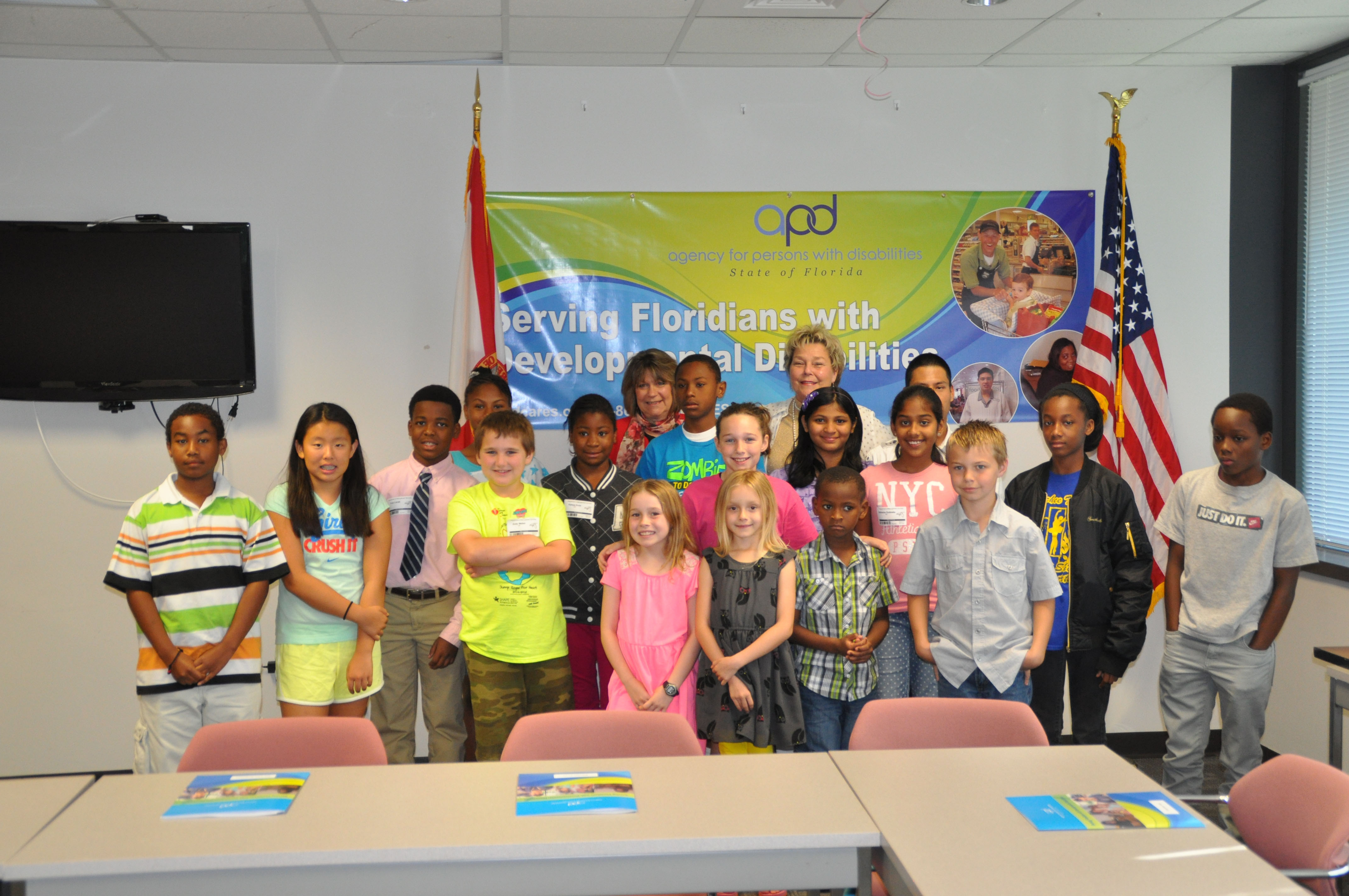 APD Chief of Staff Karen Hagan and Director Barbara Palmer, in back row, pose for a group photo with the agency's daughters and sons.