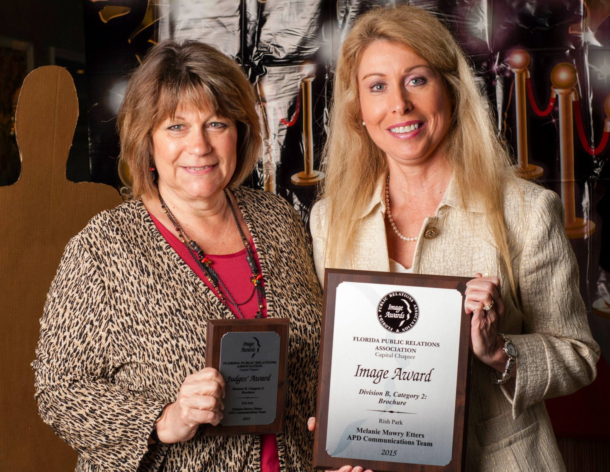 APD Chief of Staff Karen Hagan and Communications Dir. Melanie Etters hold two of APD's four awards.